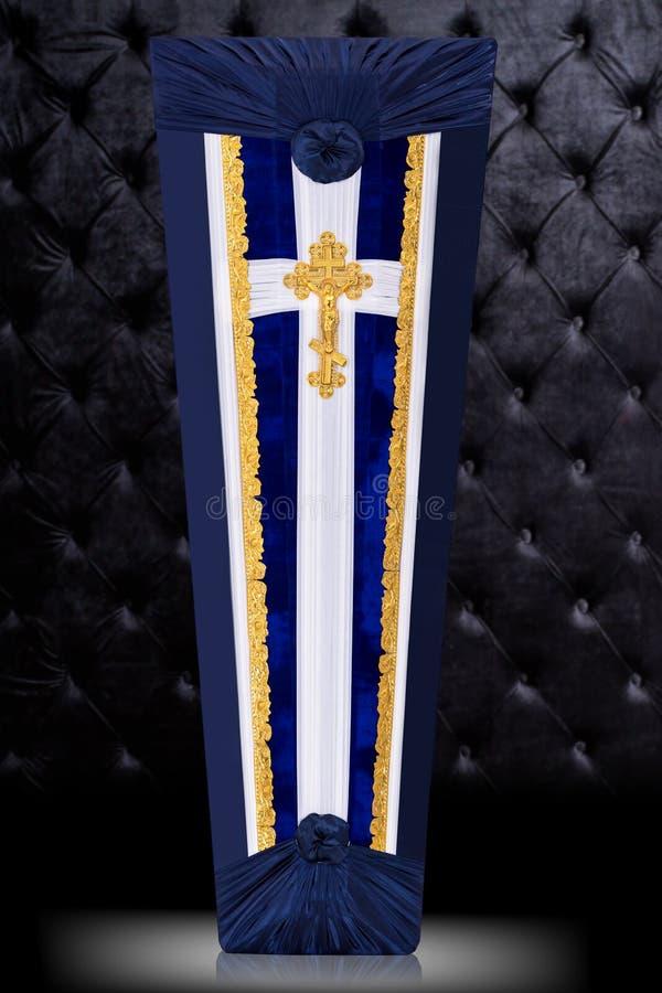 Geschlossener Sarg bedeckt mit dem blauen und wei?en Stoff verziert mit Kirchengoldkreuz auf grauem Hintergrund Vertikale Positio stock abbildung