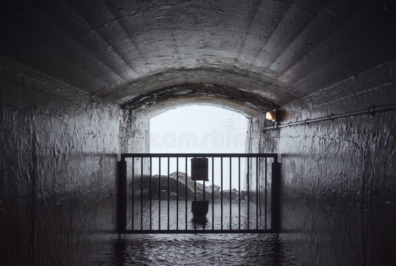 Geschlossener Tunnel, der zu einen Wasserfall führt stockfoto