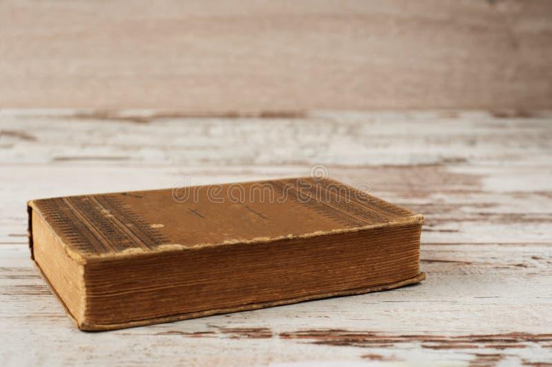 Geschlossenes altes Buch Hölzerner Hintergrund stockfoto