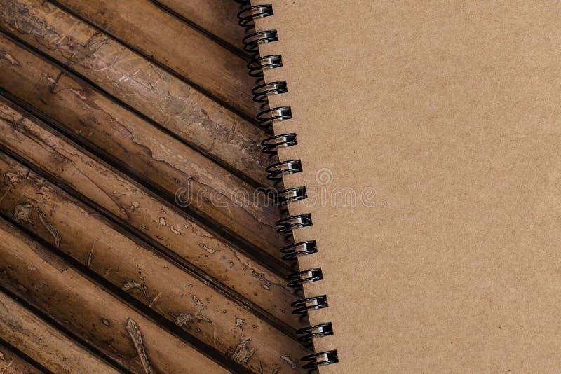 Geschlossenes Brown-Anmerkungsbuch auf einem Bambushintergrund, einfache Beschaffenheit lizenzfreie stockfotografie