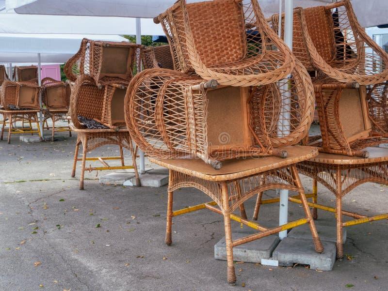 Geschlossenes Caférestaurant mit Rattan whicker Stühlen, Stockstühle gestapelt nach den Tabellen im Freien lizenzfreie stockfotos