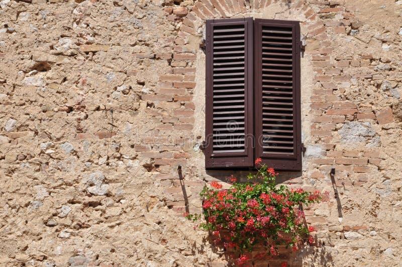 Geschlossenes Fenster auf einer Steinwand stockfotografie
