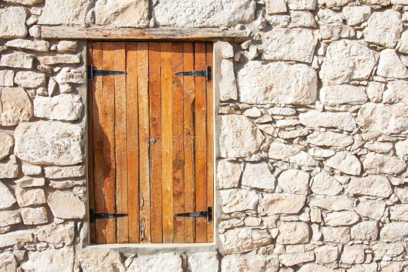 Geschlossenes hölzernes Fenster und Fensterläden in der Steinwand stockbilder