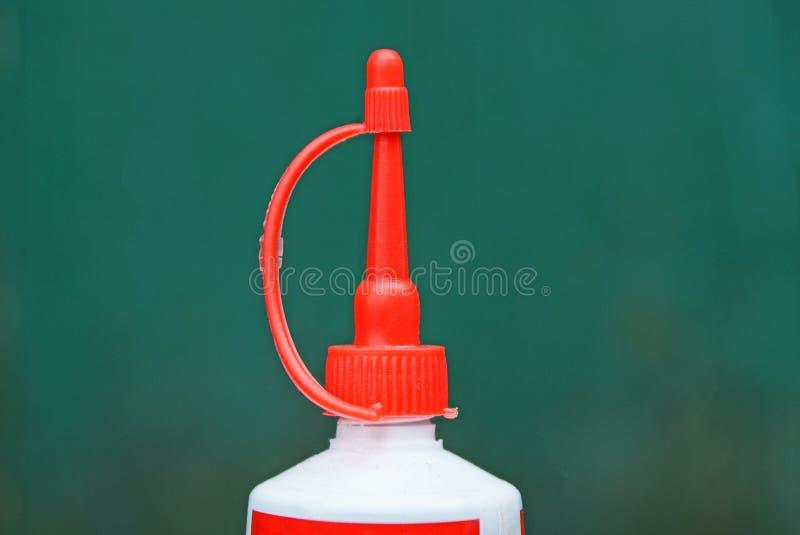 Geschlossenes Kunststoffrohr des roten Rohrs auf einem grünen Hintergrund lizenzfreie stockbilder