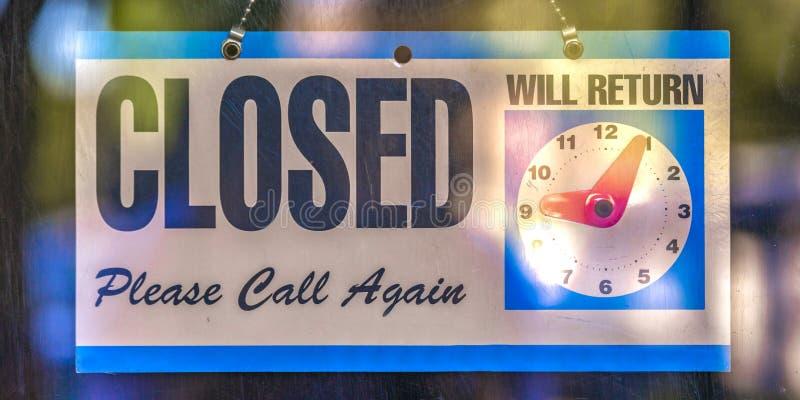 Geschlossenes Zeichen mit Uhrikone auf einer Glastür stockfotografie