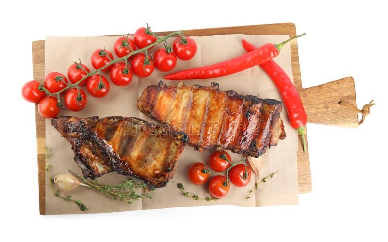 Geschmackvoll gegrillte Rippen mit Tomaten und Paprika auf weißem Boden lizenzfreie stockbilder