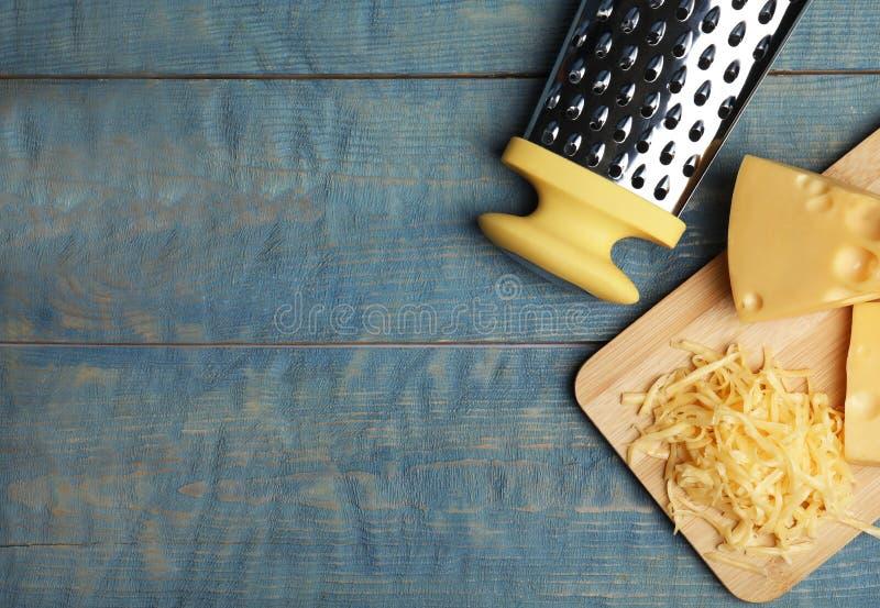 Geschmackvoll geriebener Käse auf blauem Holztisch Textbereich stockfotografie