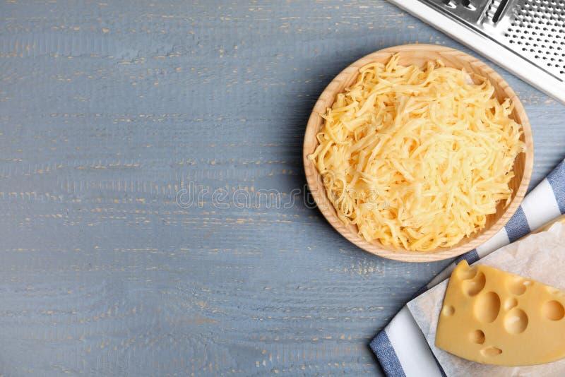 Geschmackvoll geriebener Käse auf hellgrauem Holztisch Textbereich lizenzfreie stockfotos