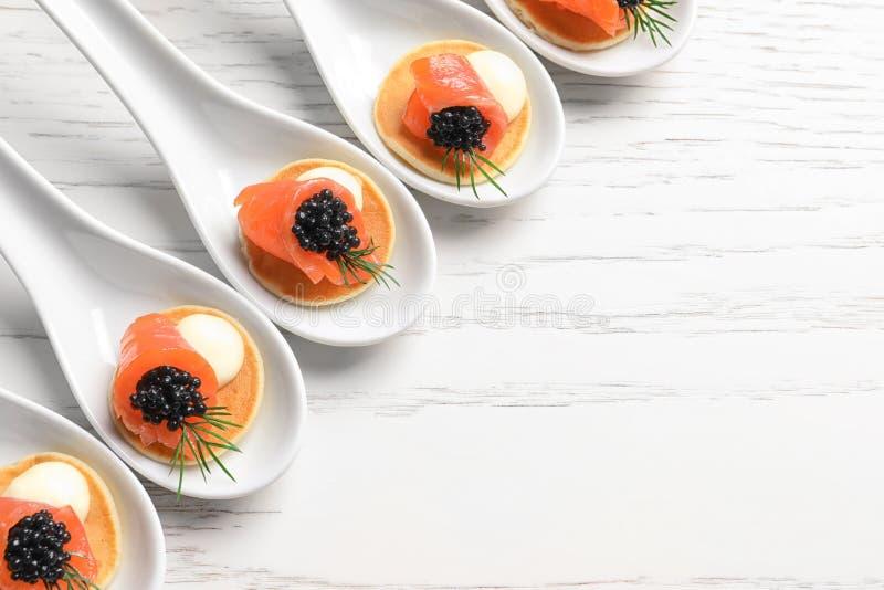 Geschmackvolle Aperitifs mit schwarzem Kaviar und Lachsen lizenzfreie stockbilder