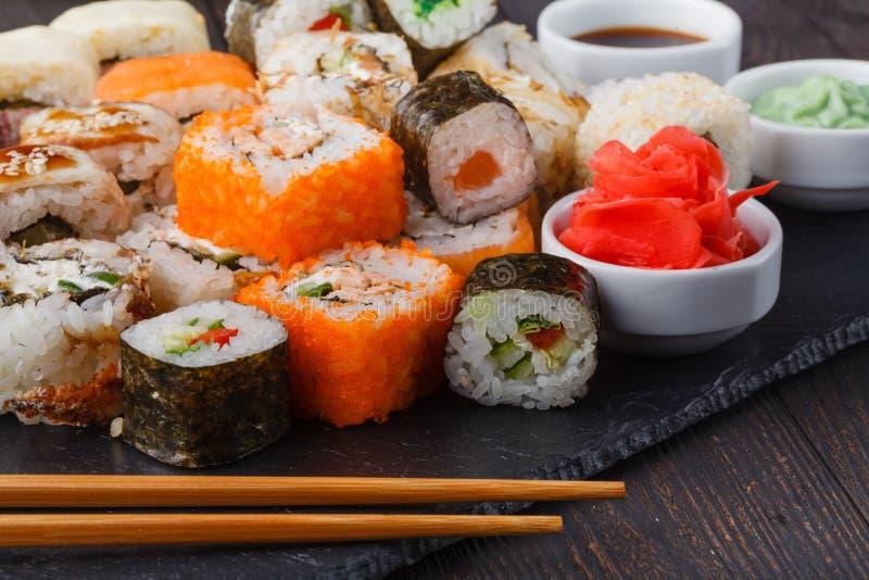 Geschmackvolle appetitanregende mehrfarbige Sushirollen eingestellt, gedient mit Sojasoße und Essstäbchen lizenzfreies stockfoto