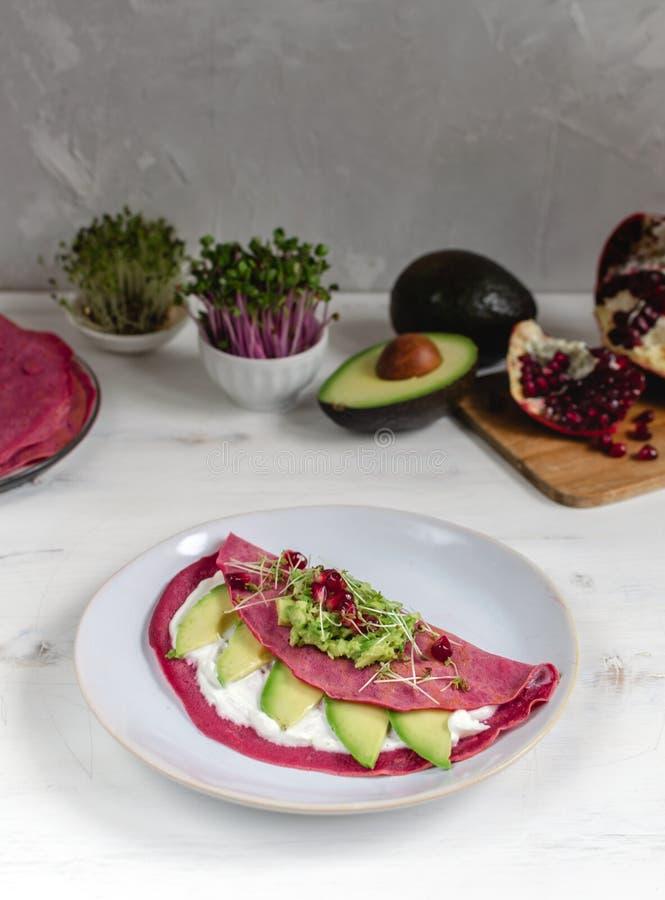 Geschmackvolle appetitanregende Rote-Bete-Wurzeln Pfannkuchen gedient auf Platte mit Avocado, Spr?sslingen und rosa Rettich, wei? lizenzfreie stockfotografie