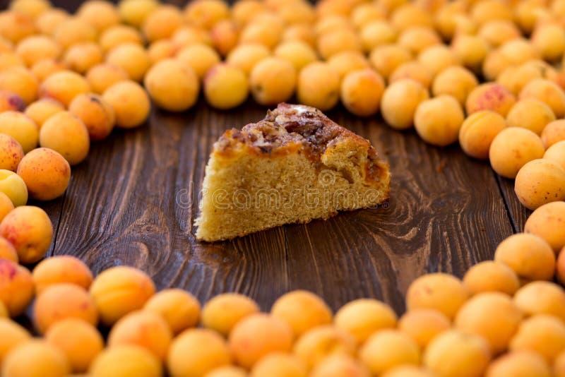 Geschmackvolle Aprikosentorte auf hölzernem Hintergrund, schnitt ein Stück des Kuchens stockfotos