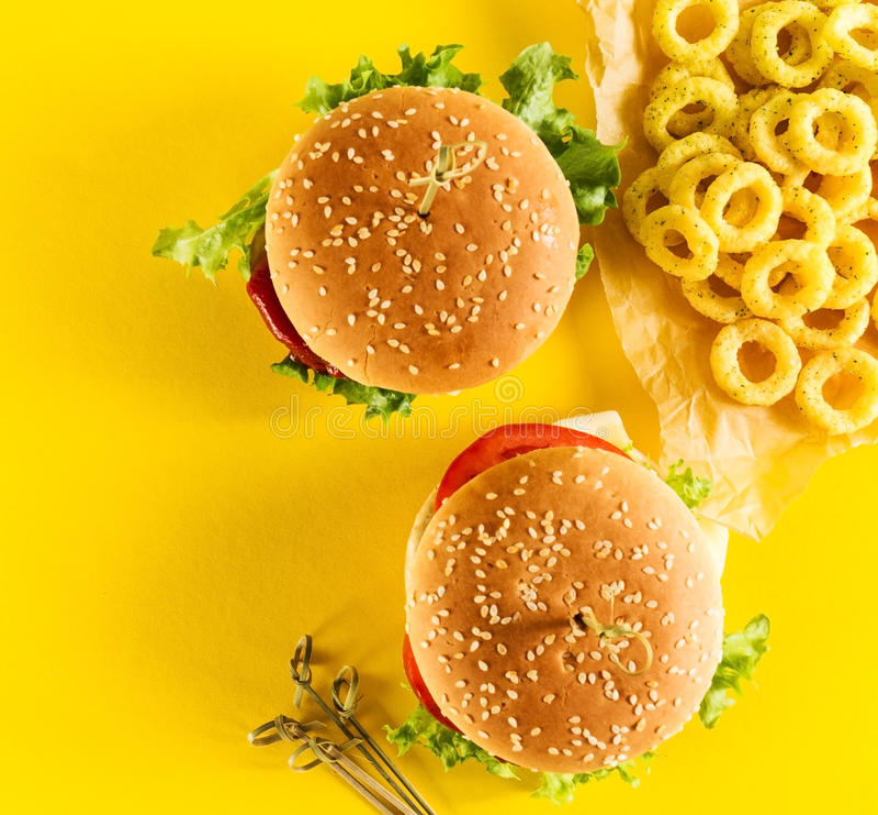 Geschmackvolle frische ungesunde Hamburger mit Ketschup und Gemüse und lizenzfreies stockfoto