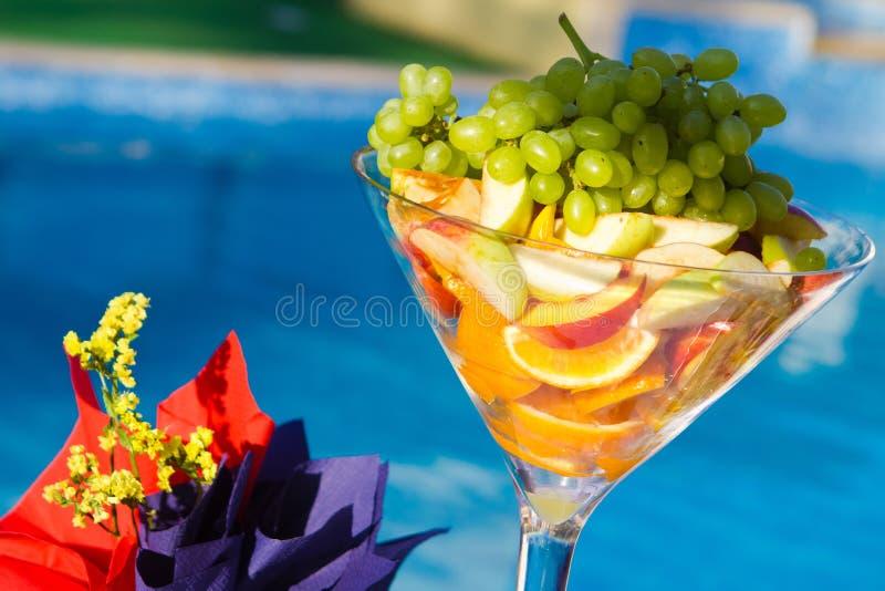 Geschmackvolle Fruchtorangen, -äpfel und -trauben in einem Glasvase am Parteibankett, Lebensmittelfoto lizenzfreies stockfoto