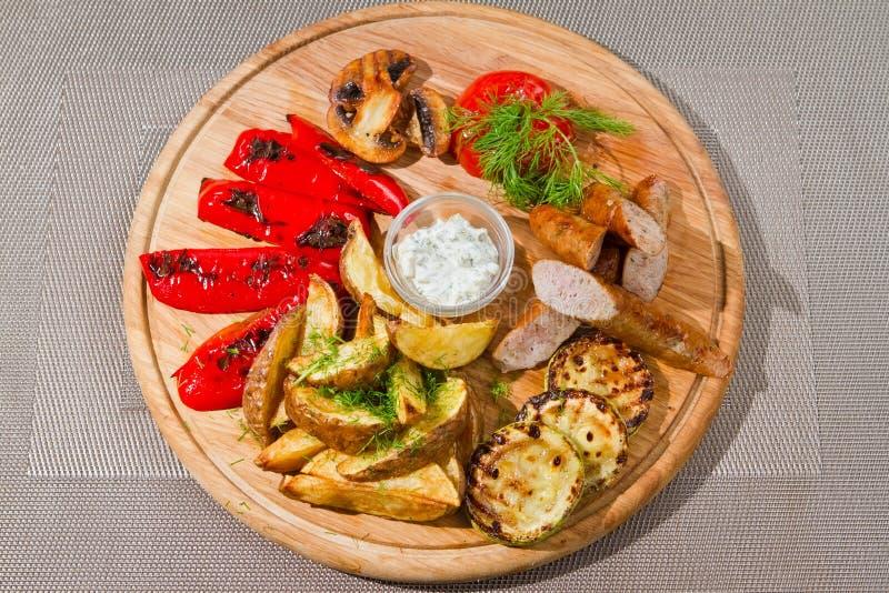 Geschmackvolle geräucherte Würste mit gegrillten Tomaten, Paprika, Pilze, Zucchini, brieten Kartoffeln, Dill, weiße saure Soße stockfotografie