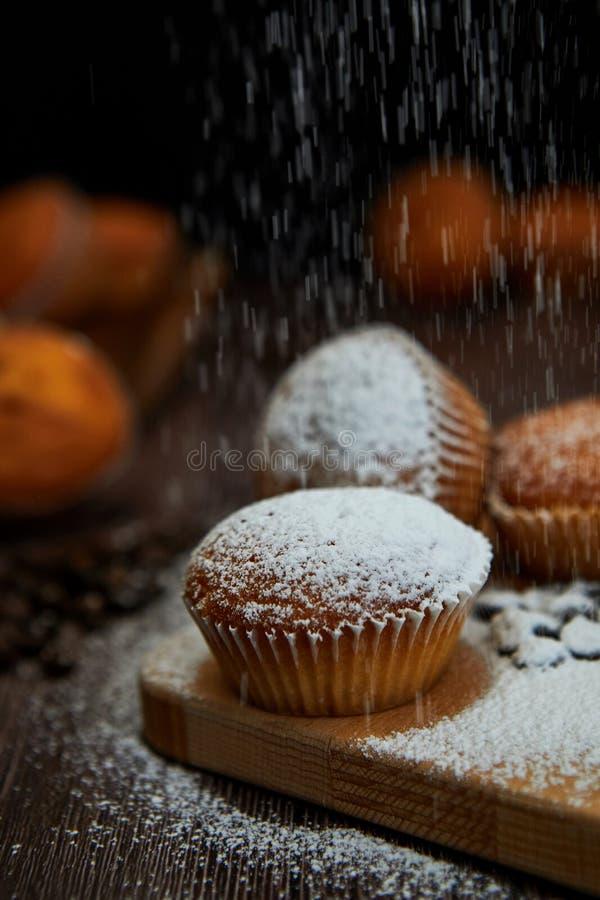 Geschmackvolle Muffinnahaufnahme auf einem h?lzernen Brett bespr?ht mit Puderzucker, selektiver Fokus stockfotos