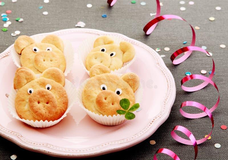 Geschmackvolle nette Schweinplätzchen mit Blättern auf rosa Platte stockfotografie
