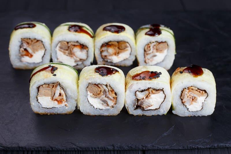 Geschmackvolle neue maki Sushirolle mit Aal und unagi sauce, bedeckte wi stockfotografie