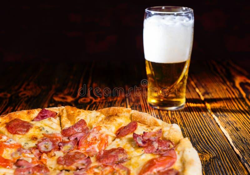 Geschmackvolle Pepperonipizza auf Holztisch nahe einem Glas Bier lizenzfreies stockfoto