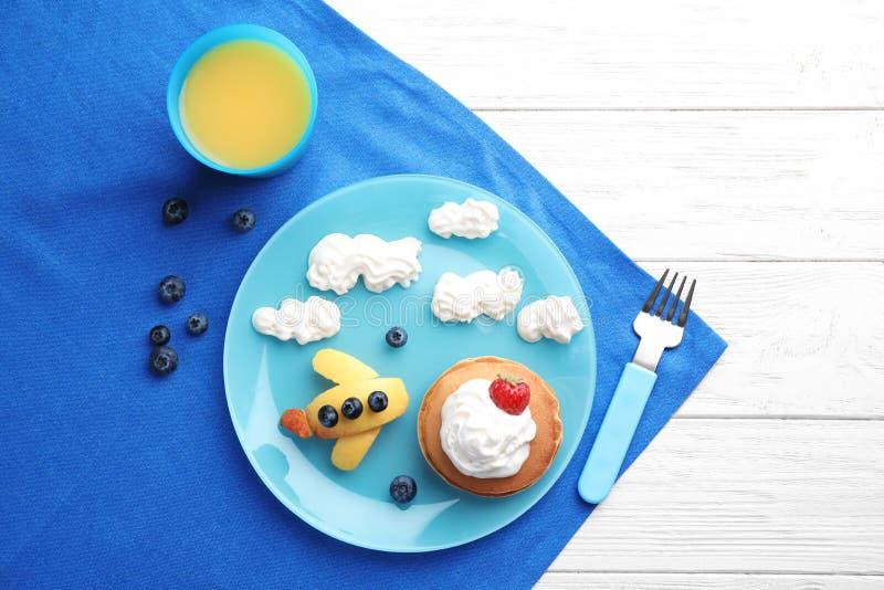 Geschmackvolle Pfannkuchen mit Beeren, Sahne und Saft auf weißem Holztisch Kreative Idee für ein Kinderfrühstück stockfotos