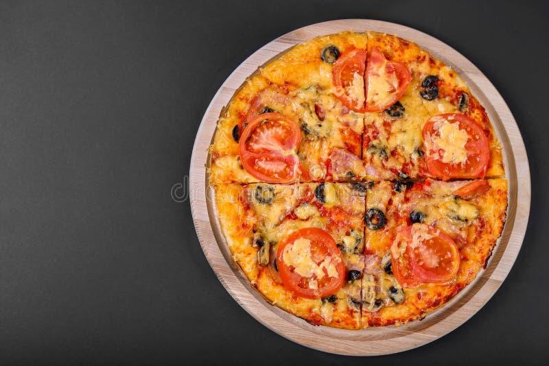 Geschmackvolle Pizza auf einem schwarzen Hintergrund Draufsicht der heißen Pizza Flache Lage fahne lizenzfreie stockbilder