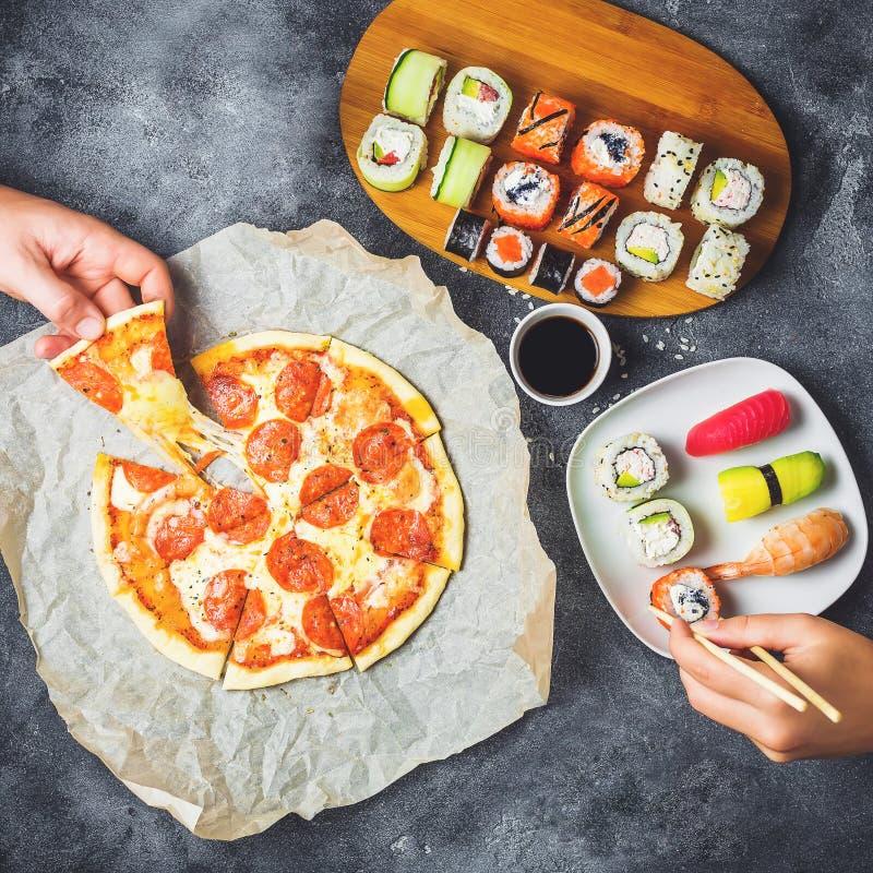 Geschmackvolle Pizza mit Salami, Satz Sushirollen und Hände nehmen Lebensmittel Dunkler Hintergrund Flache Lage, Draufsicht stockfotos
