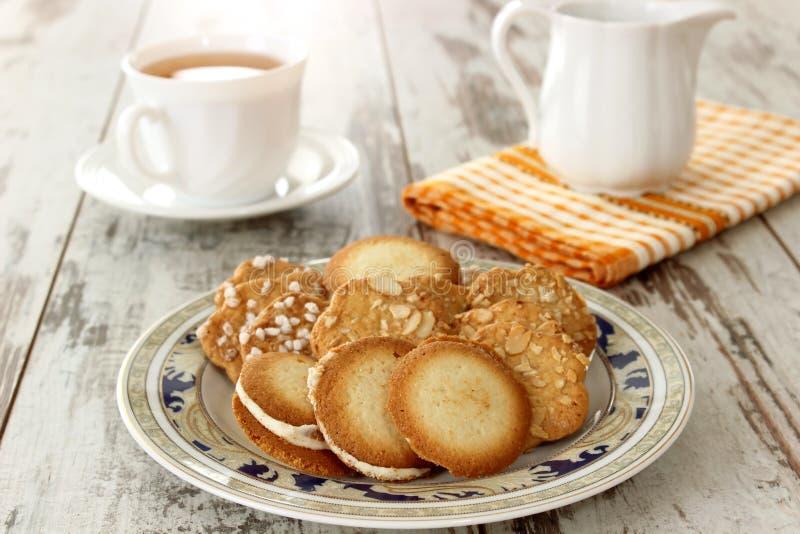 Geschmackvolle Plätzchen auf schöner Platte und Tasse Tee lizenzfreie stockfotos