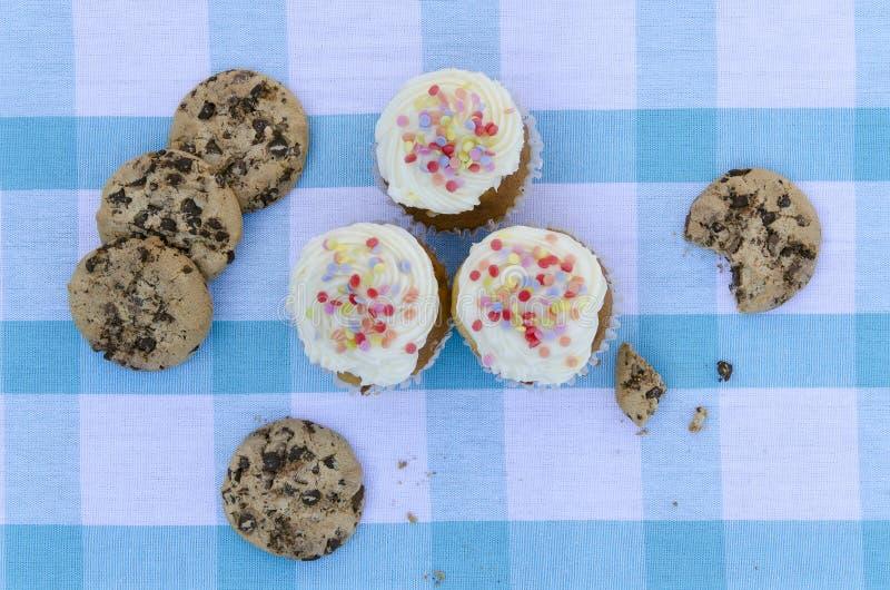 Geschmackvolle Plätzchen und Muffinkuchen mit der Vanillecreme verziert mit Zuckersüßigkeiten auf einem hölzernen Hintergrund stockbild