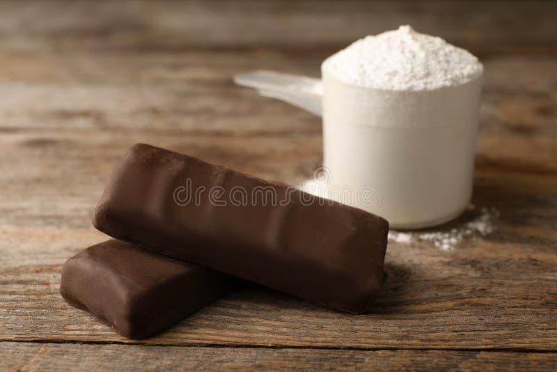 Geschmackvolle Proteinstangen und Schaufel des Pulvers stockfotos