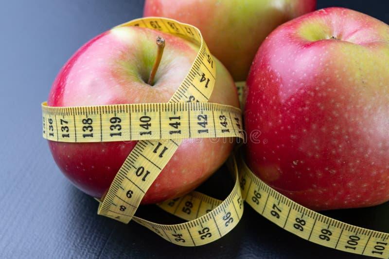 Geschmackvolle, reife Äpfel wickelten in einem messenden Band ein Frucht auf einer dunklen Tabelle lizenzfreies stockfoto