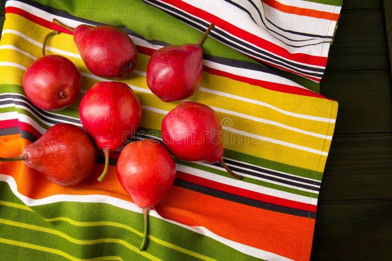 Geschmackvolle reife Birnen auf buntem Stoff stockfoto