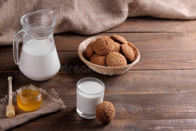 Geschmackvolle süße Hafermehlplätzchen mit Milch und Honig auf einem braunen Holztisch stockfotos