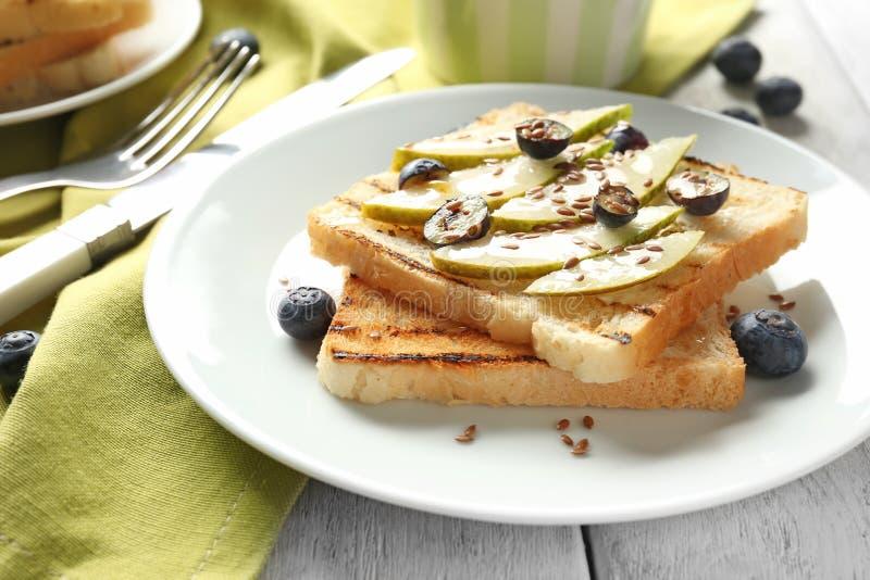 Geschmackvolle süße Toast mit geschnittener Birne und Blaubeere auf Platte stockfoto