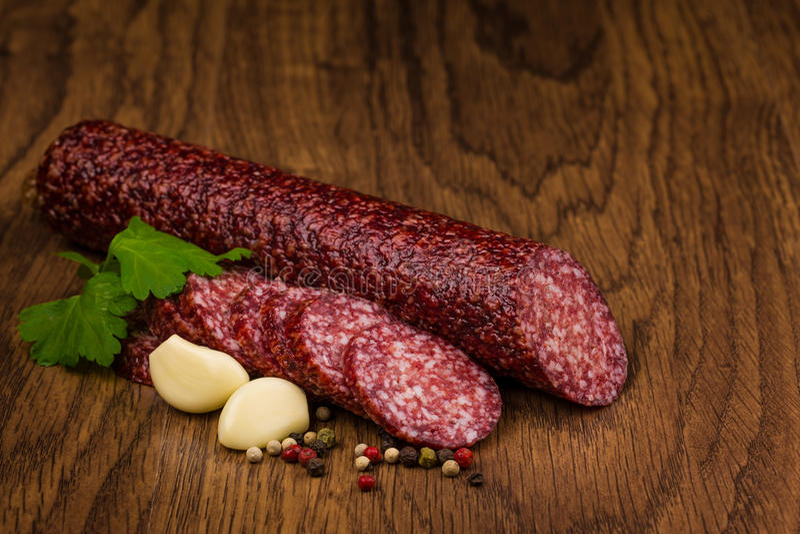 Geschmackvolle Salamiwurst auf hölzernem Hintergrund stockbild