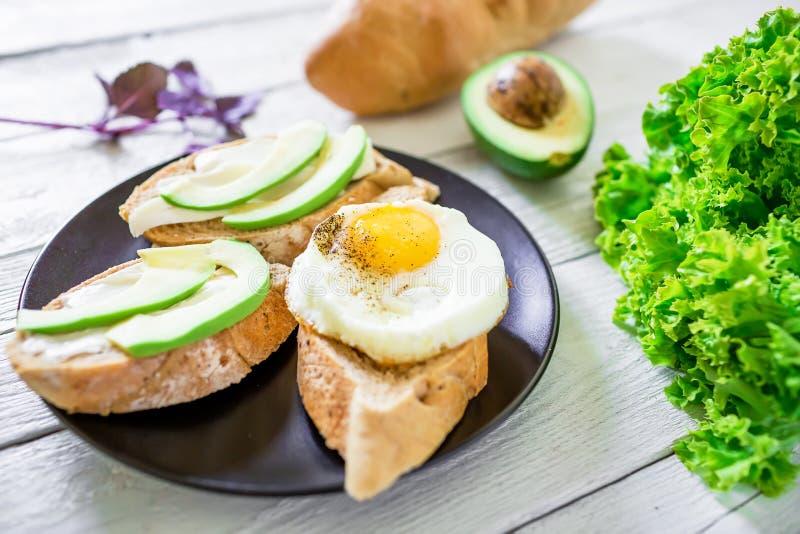 Geschmackvolle Sandwiche mit Avocado und Ei auf einer dunklen Platte auf hölzernem Hintergrund stockfotografie