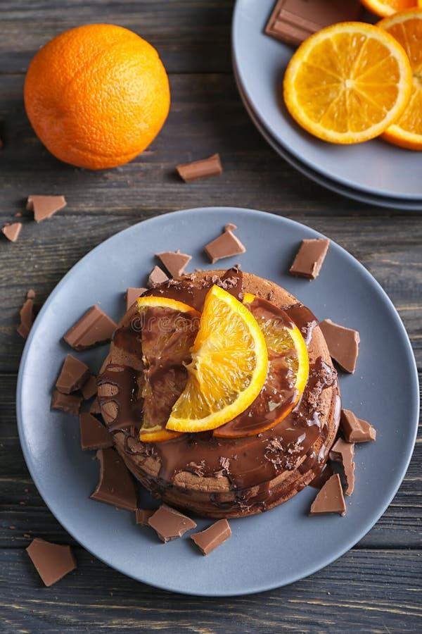 Geschmackvolle Schokoladenpfannkuchen mit süßer Soße und geschnittener Orange auf Platte lizenzfreies stockfoto