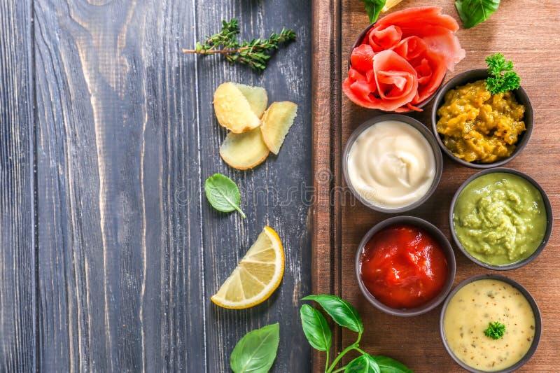 Geschmackvolle Soßen in den Schüsseln mit Kräutern auf Holztisch lizenzfreies stockfoto