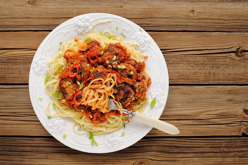Geschmackvolle Spaghettis mit Fleischklöschen in Tomate sause auf Holztisch O stockfotografie