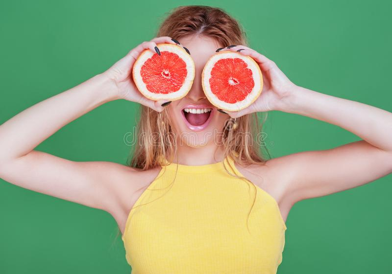 Geschmackvolle tropische Früchte! Attraktive sexuelle Frau mit dem schönen Make-up, das frische saftige Pampelmuse oder orange na stockfoto