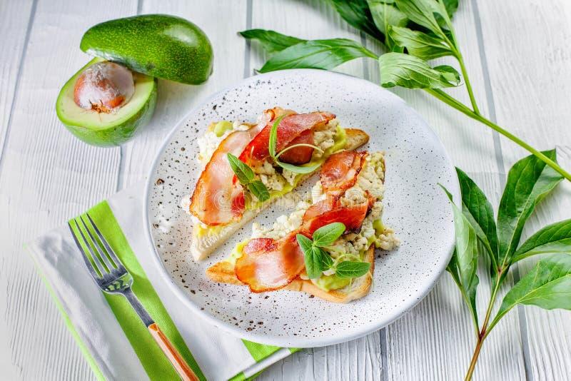 Geschmackvolle und Ernährungssandwiche mit Speck und Ei mit Avocado lizenzfreies stockfoto