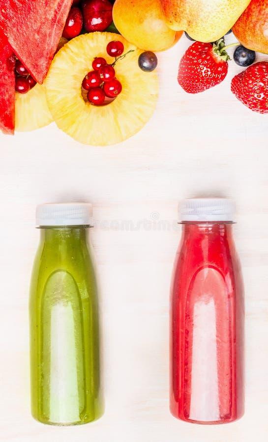 Geschmackvolle und gesunde Sommergetränke in den Flaschen mit Früchten und Beerenbestandteil Roter und grüner Smoothie oder Saft  lizenzfreies stockfoto