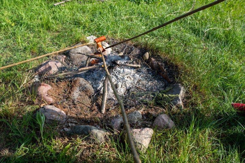 Geschmackvolle Würste, die mit dem Fett gebacken auf einem offenen Feuer tropfen Ein Kamin in einem Hausgarten lizenzfreie stockfotos