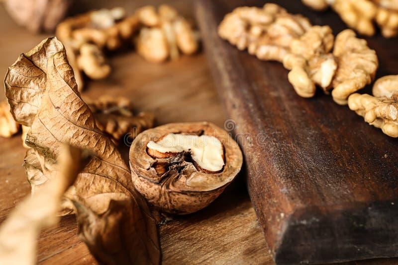 Geschmackvolle Walnüsse mit trockenem Blatt auf Holztisch lizenzfreies stockbild