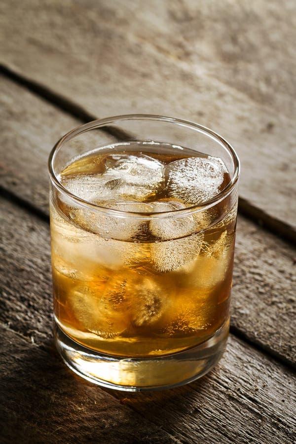 Geschmackvoller bunter kalter Alkohol-Getränk-Whisky mit Eis im Glas auf W stockbilder