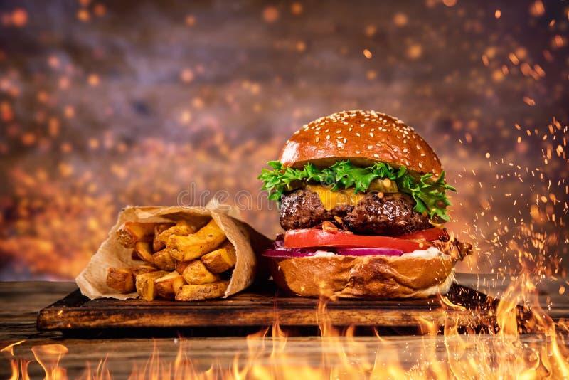 Geschmackvoller Burger mit Pommes-Frites und Feuer lizenzfreies stockbild