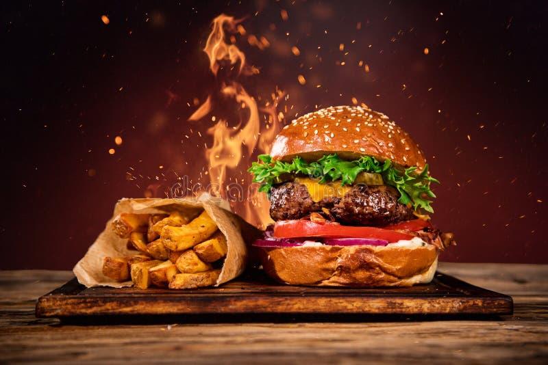 Geschmackvoller Burger mit Pommes-Frites und Feuer stockfoto
