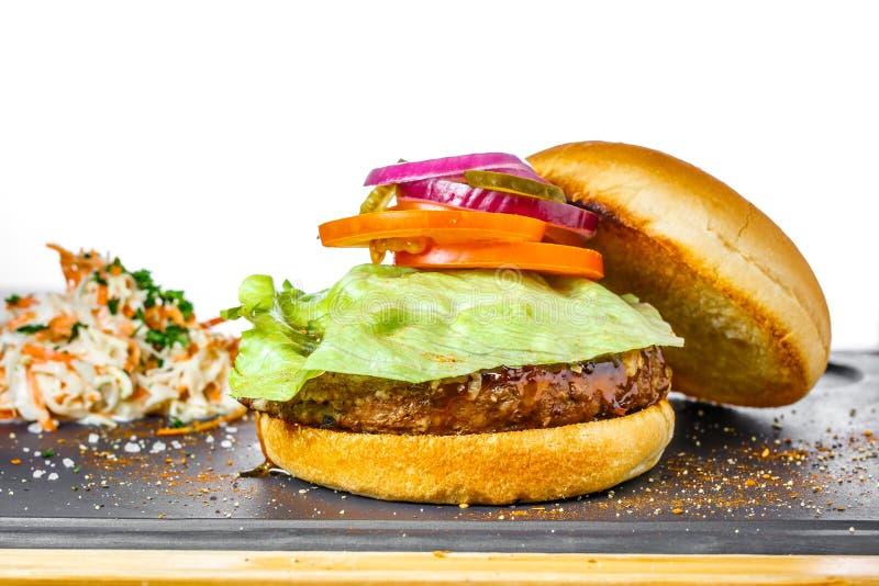 Geschmackvoller Burger mit Rindfleischkotelett auf weißem Hintergrund bestandteile stockbild