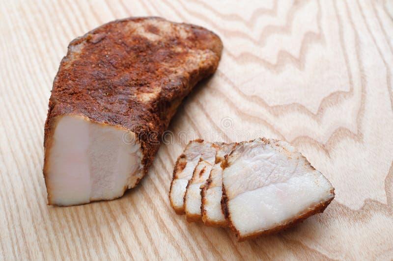 Geschmackvoller geräucherter Schweinefleischschinken mit Gewürzen Schneiden Sie in Scheiben auf einem hölzernen BAC stockfotos