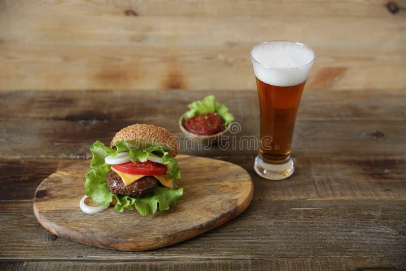 Geschmackvoller Hamburger mit Glasbier auf einem hölzernen rustikalen Hintergrund mit Kopienraum für Text Beschneidungspfad einge lizenzfreie stockbilder