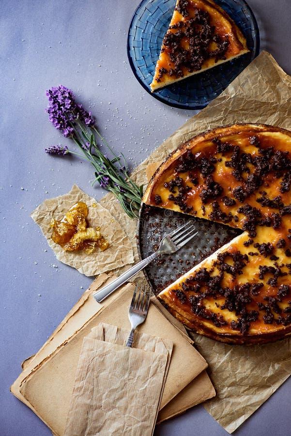 Geschmackvoller Käsekuchen mit Schokoladenkeksen und -honig Dekoration des Honigs und des Lavendels lizenzfreie stockbilder